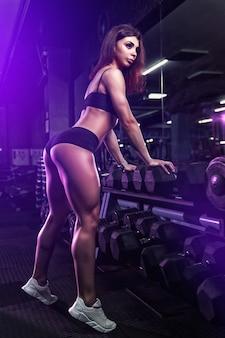 Garota fitness, exercitando e posando com peso no ginásio.