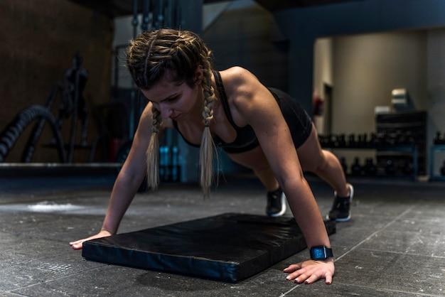 Garota fitness fazendo exercício flexionando