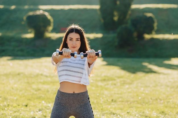 Garota fitness fazendo exercícios com halteres no pôr do sol na grama do lado de fora
