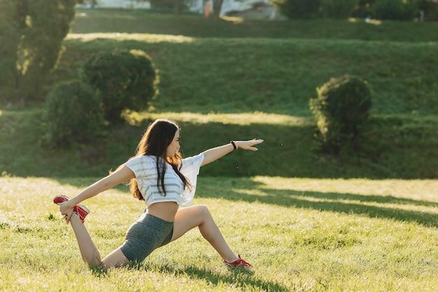 Garota fitness fazendo exercícios de alongamento fora na luz do sol uma grama