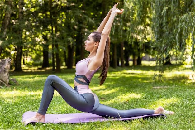 Garota fitness fazendo exercícios no gramado em um parque
