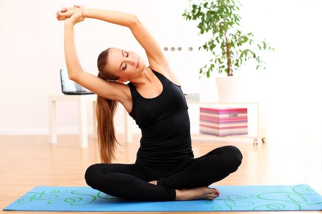 Garota fitness fazendo yoga em casa