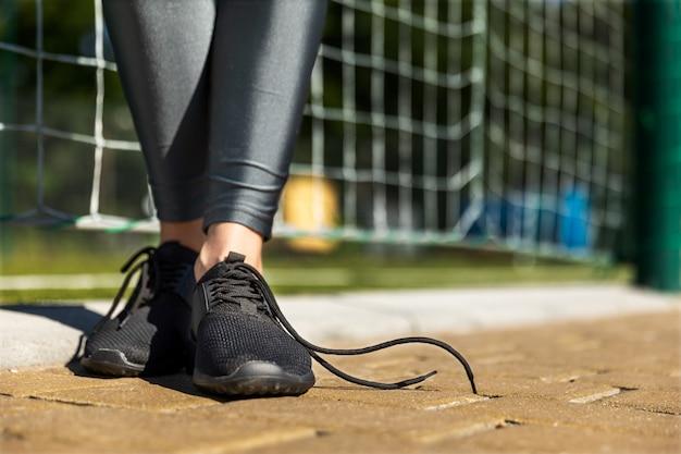 Garota fitness fica em uma pista com atacadores soltos
