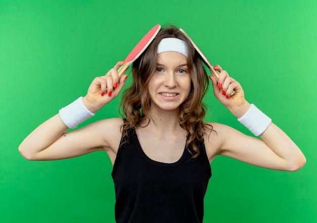Garota fitness jovem em roupa esportiva preta com bandana segurando duas raquetes de tênis de mesa na cabeça, sorrindo confusa em pé sobre a parede verde
