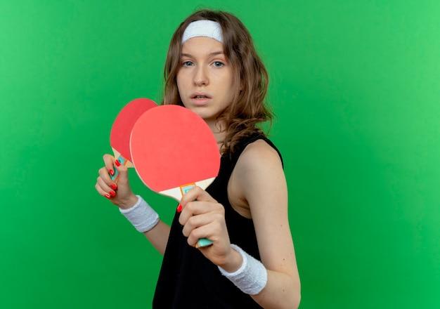 Garota fitness jovem em roupa esportiva preta com fita para a cabeça segurando duas raquetes de tênis de mesa com cara séria em pé sobre a parede verde