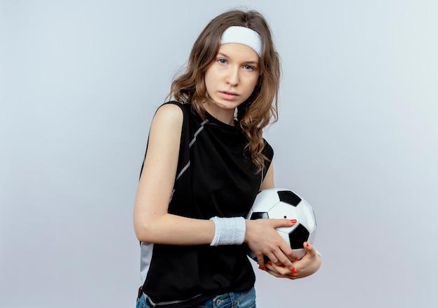 Garota fitness jovem em roupa esportiva preta com tiara segurando uma bola de futebol descontente em pé sobre uma parede branca