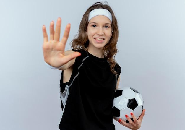 Garota fitness jovem em sportswear preto com tiara segurando uma bola de futebol, fazendo sinal de pare com a mão aberta, sorrindo em pé sobre uma parede branca