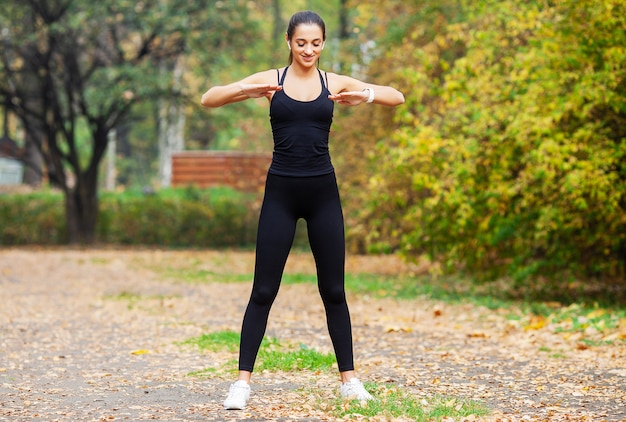 Garota fitness, jovem mulher fazendo exercícios no parque.