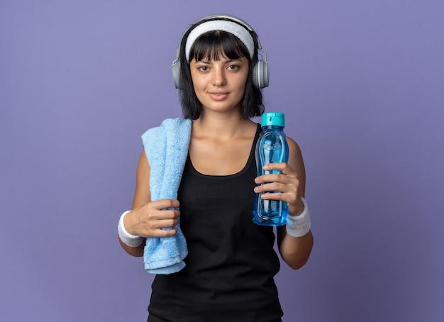 Garota fitness jovem usando bandana com fones de ouvido e uma toalha no ombro segurando uma garrafa de água, olhando para a câmera com um sorriso confiante no rosto em pé sobre um fundo azul