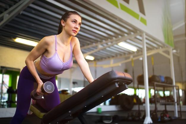 Garota fitness levantando halteres pela manhã.