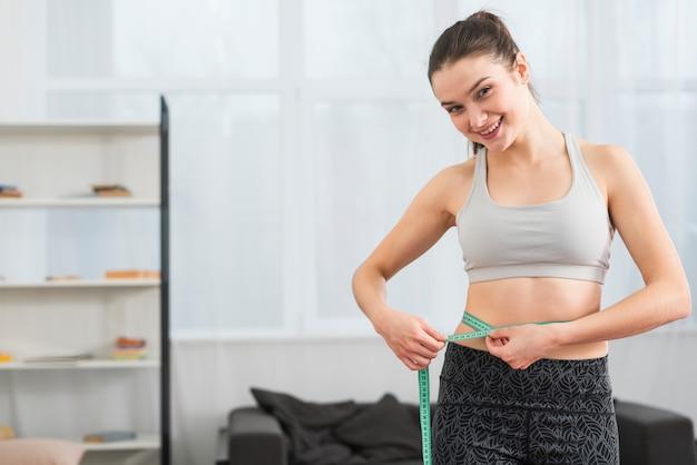 Garota fitness medindo-se