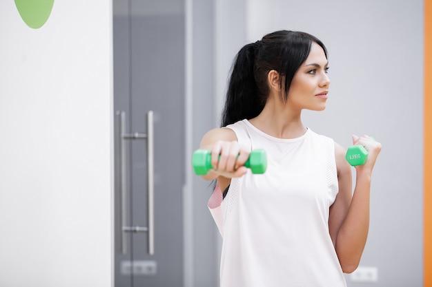 Garota fitness, mulher adolescente malhando na academia com halteres