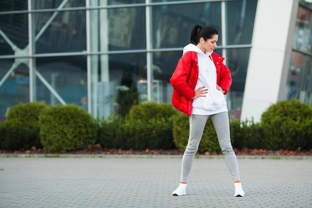 Garota fitness. mulher jovem esportes, estendendo-se na cidade moderna. estilo de vida saudável na cidade grande