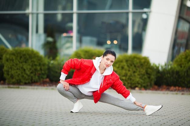 Garota fitness. mulher nova dos esportes que estica na cidade moderna. estilo de vida saudável na cidade grande