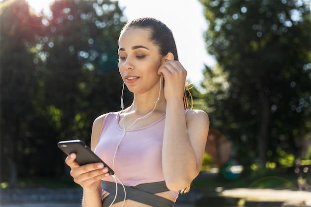 Garota fitness ouvindo música fica na rua