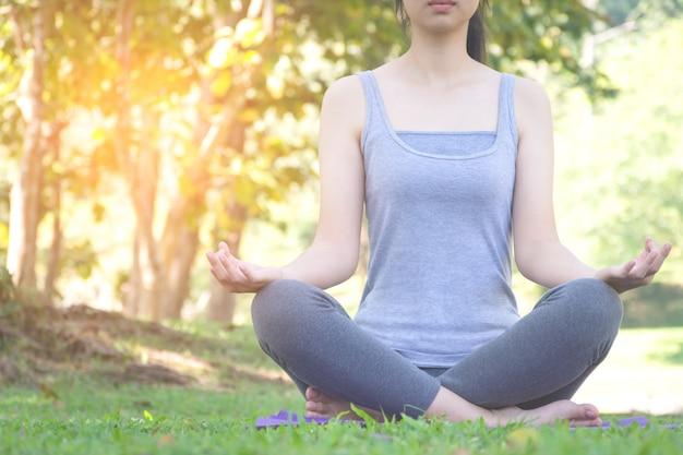 Garota fitness praticando yoga no parque com a luz do sol