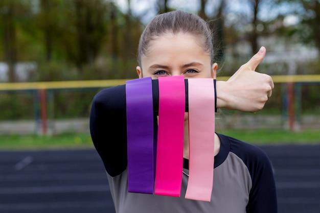 Garota fitness segurando três trechos de goma fitness