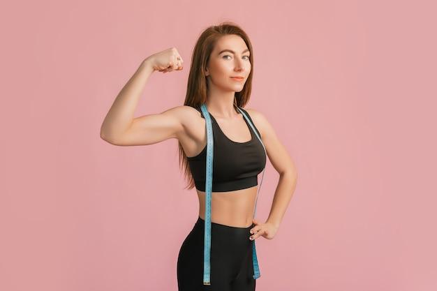 Garota fitness sorrindo e posando segurando a fita métrica em uma roupa esportiva preta em um espaço rosa