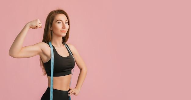 Garota fitness sorrindo e posando segurando a fita métrica em uma roupa esportiva preta em uma superfície rosa