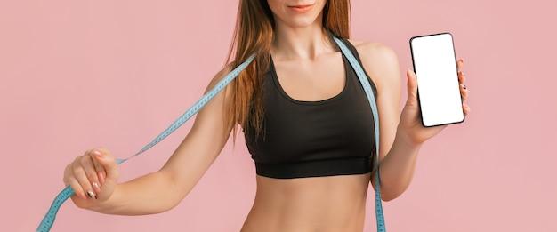 Garota fitness sorrindo e segurando um telefone com uma maquete e posando segurando a fita métrica em um sportswear preto em um espaço rosa