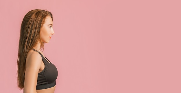 Garota fitness sorrindo em uma roupa esportiva preta em uma superfície rosa