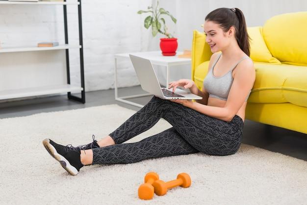 Garota fitness trabalhando com laptop