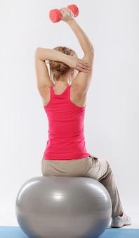 Garota fitness treina no ginásio na bola de fitness