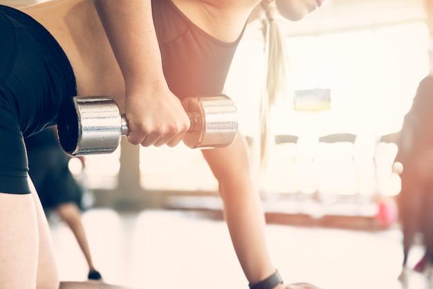 Garota fitness usando dumbball