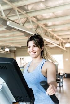 Garota fitness usando instrutor elíptico
