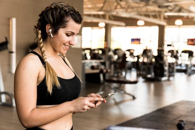 Garota fitness usando seu telefone celular
