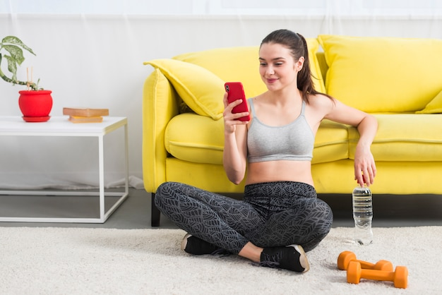 Garota fitness usando seu telefone móvel