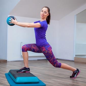 Garota fitness, vestindo tênis posando no degrau com bola