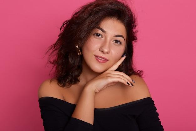 Garota flertando com ombros nus, vestindo camisa preta elegante posando contra parede rosa
