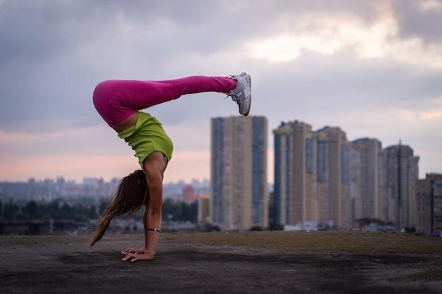 Garota flexível mantém o equilíbrio nas mãos no fundo da paisagem urbana