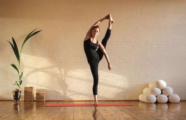 Garota flexível praticando ioga em um estúdio