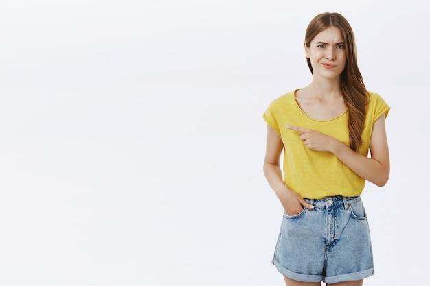 Garota fofa cética descontente apontando o dedo para a esquerda e sorrindo incomodada