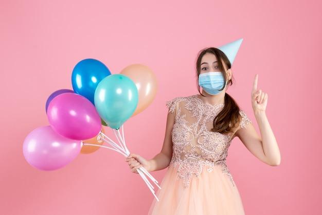 Garota fofa de vista frontal com boné segurando balões coloridos apontando com o dedo para cima