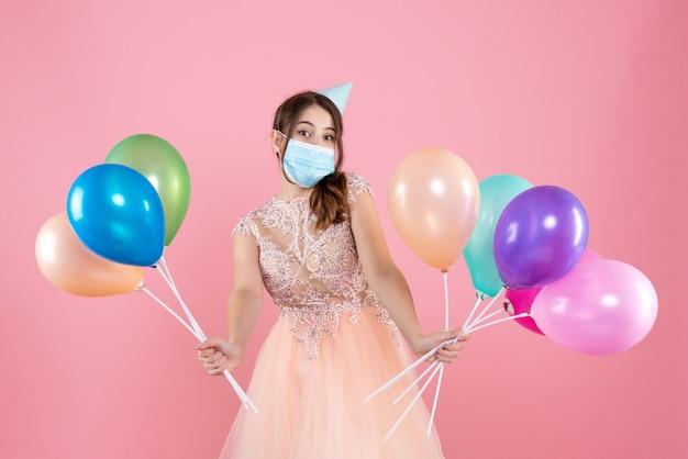 Garota fofa de vista frontal com chapéu de festa e máscara médica segurando balões coloridos com as duas mãos