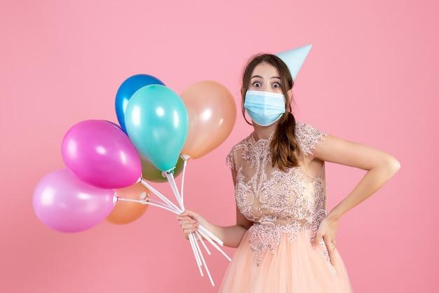 Garota fofa de vista frontal com chapéu de festa segurando balões coloridos colocando a mão