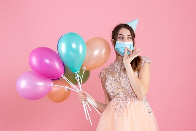 Garota fofa de vista frontal com chapéu de festa segurando balões coloridos