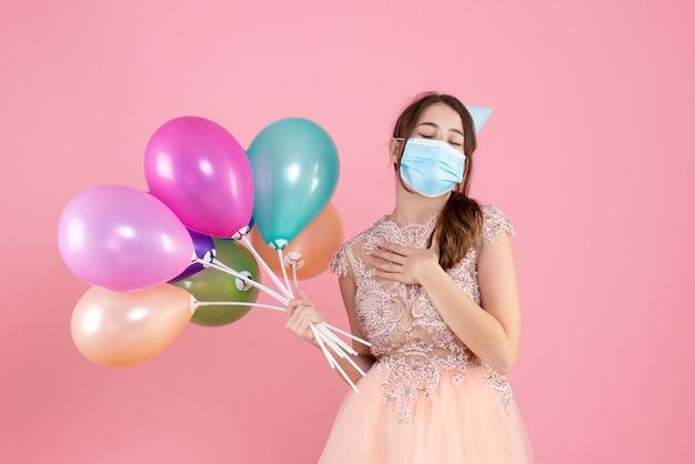 Garota fofa de vista frontal com tampa de festa fechando os olhos segurando balões coloridos