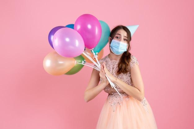 Garota fofa de vista frontal com tampa de festa segurando balões coloridos fazendo um pedido