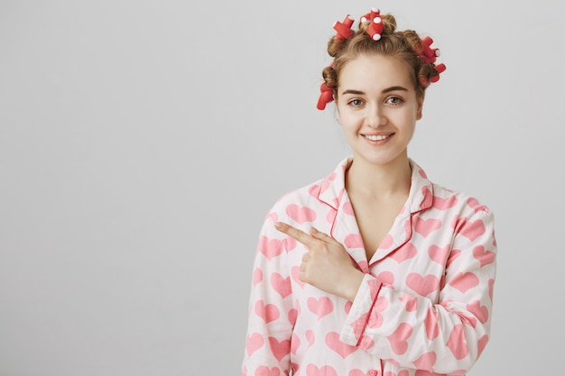 Garota fofa surpresa e curiosa em pijamas e rolos de cabelo apontando o dedo para a esquerda no banner