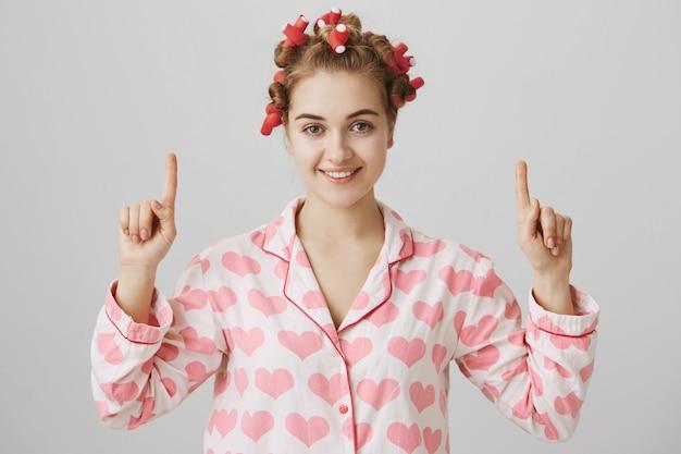 Garota fofa surpresa e curiosa em pijamas e rolos de cabelo apontando o dedo para o anúncio