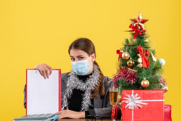 Garota forte de frente com máscara médica sentada à mesa árvore de natal e coquetel de presentes