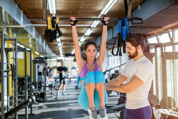 Garota forte e apta fazendo abdominais na academia com a ajuda de seu treinador pessoal de fitness.