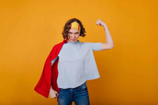 Garota forte na coroa mostrando músculos