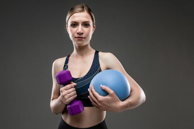Garota forte no sportswear segura uma bola de esportes e um haltere em uma parede preta