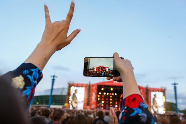 Garota fotográfica curtindo show de rock, mão levantada e batendo palmas de prazer, fotografando por smartphone
