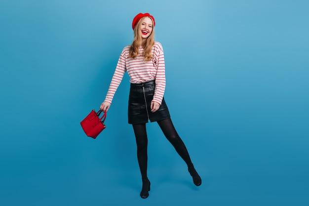 Garota francesa animada com saia curta dançando na parede azul. vista do comprimento total da incrível mulher loira segurando a bolsa vermelha.